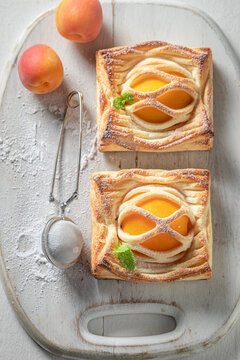 Delicious puff pastry with peaches and mint. French juicy dessert.