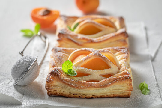 Homemade puff pastry with sugar and peaches. French juicy dessert.