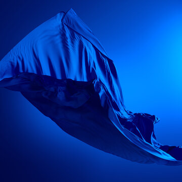 3d render. Abstract fashion background with silk scarf falling down. Dramatic scene with blue drapery blown away by the wind