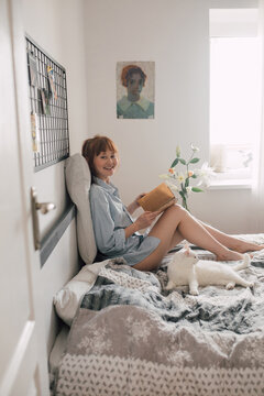 Woman looking at the camera while enjoying leisure weekend time with favorite novel