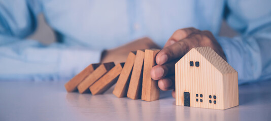 Hands of businessman stop risk about home with block wooden and safety, investment and insurance about real estate and property, planning and strategy, loan and debt of house, business concept. - fototapety na wymiar