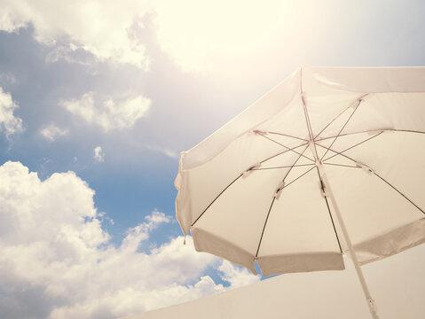White beach umbrella against sunny sky.