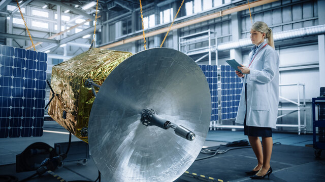 Female Engineer Uses Digital Tablet Computer while Working on Satellite Construction. Aerospace Agency: Scientist Overseeing Building and Assembly of Spacecraft for Space Exploration Mission