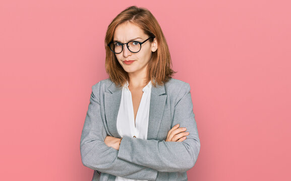 Young caucasian woman wearing business style and glasses skeptic and nervous, disapproving expression on face with crossed arms. negative person.