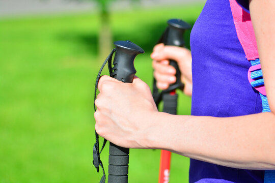 Nordic walking background. Female hands with a walking sticks close-up.