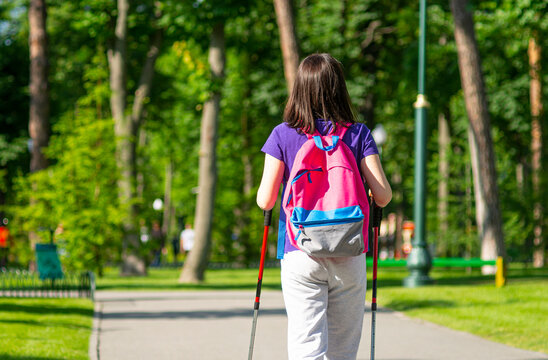 Scandinavian walking. Girl with a walking sticks in the park.