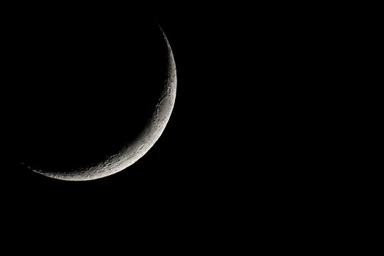 A waxing crescent moon rises over the town of Elefsina
