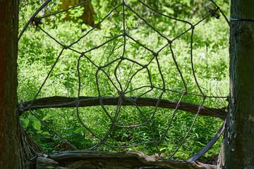 Gigantyczna pajęcza sieć rozpięta pomiędzy drzewami i wykonana z grubego sznura.  - fototapety na wymiar