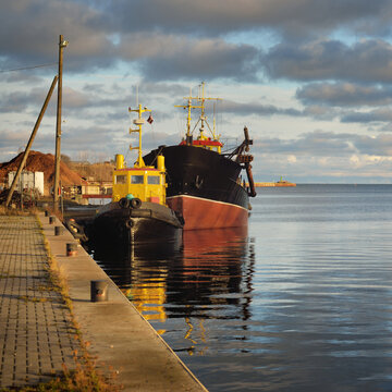 Small ship and fishing boat moored to a pier in a harbor at sunset. Baltic sea, Latvia. Idyllic winter seascape. Industry, business, transportation, service, logistics, delivery, shipping