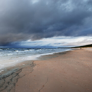 Panoramic view of the Baltic sea at sunset. Dramatic sky with dark glowing cumulus clouds. Water surface texture close-up. Fickle weather, winter, climate change, nature, environment