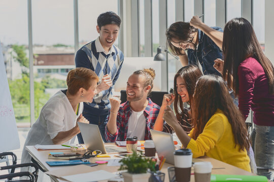 Group Of Asian and Multiethnic Business people with casual suit working with happy action and celebrate when project is completed in the modern workplace, people business group concept