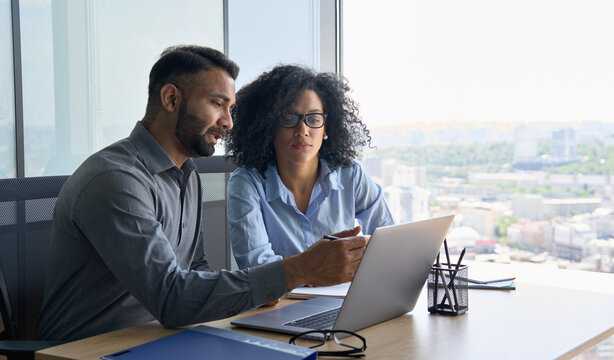 Indian male ceo executive manager mentor giving consultation on financial operations to female African American colleague intern using laptop sitting in modern office near panoramic window.