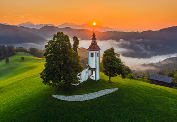 Skofja Loka, Slovenia - Aerial view of the beautiful hilltop church of Sveti Tomaz (Saint Thomas) with amazing golden foggy sunrise and the Julian Alps at background at summer time