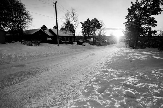 Rural street, in winter in the Republic of Karelia, Russia. Black and white photo.