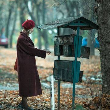 A woman takes a letter out of an old mailbox outdoor.