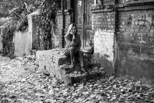 Elegant woman in a jacket sits on the porch of an old house with maple leaves on the ground in the autumn day atmosphere. Black and white photo.