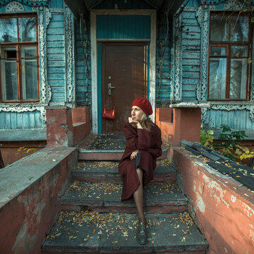 Woman in a burgundy coat and beret is patiently waiting sitting on the porch of an old wooden house.