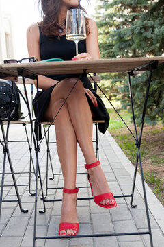 Beautiful woman with long sexy legs having a rest in the street restaurant . Model sitting in an armchair in a cafe..