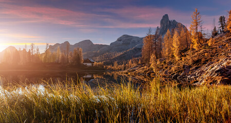 Magic sunny morning scene in autumn forest. Splendid Alpine lake in mountain valley with colorful sky during sunset. Amazing nature landscape. Wonderful natural background. Vivid wallpaper