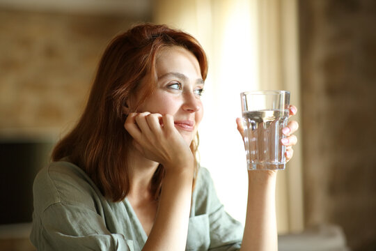 Satisfied woman holding water glass at home contemplating
