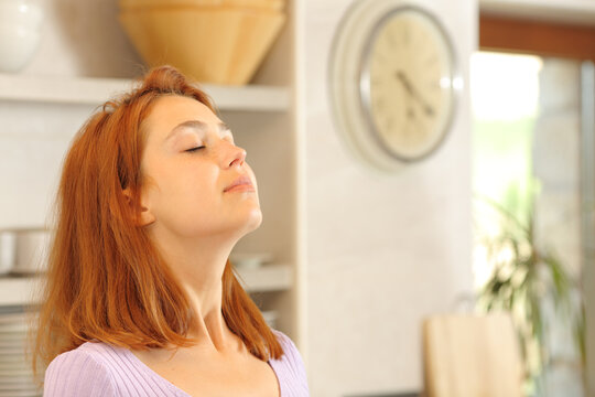 Woman breathing fresh air in the kitchen
