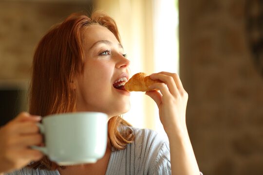 Woman eating and drinking for breakfast at home