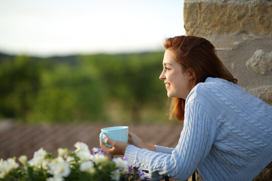Happy woman contemplating from balcony with coffee cup