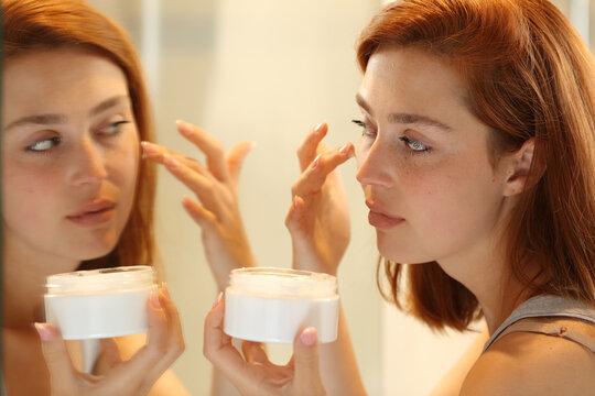 Woman hydrating face skin applying moisturizer cream