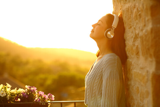 Woman resting in a balcony listening to music with headphones