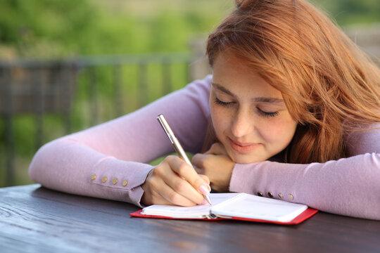 Woman writing on agenda in a balcony