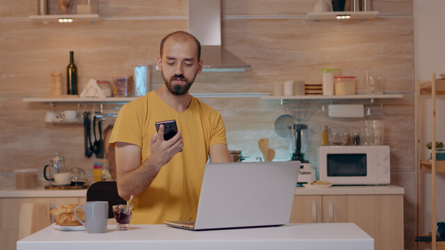 Man working from house with automation lighting system, sitting in kitchen switch off the lights using voice command to smart home application on smartphone. Person controlling light with wifi gadget