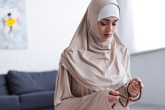 young muslim woman with rosary praying with closed eyes at  home