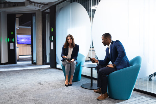 Diverse businessman and businesswoman discussing together while sitting at modern office