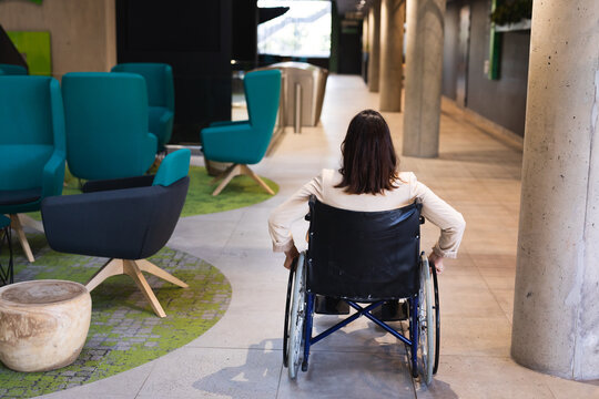 Rear view of disabled caucasian businesswoman sitting on wheelchair at modern office
