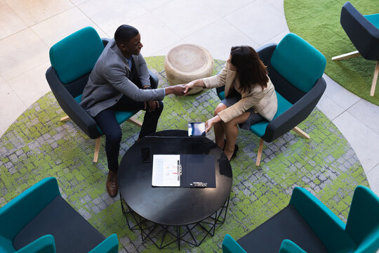 Overhead view of diverse businessman and businesswoman shaking hands at modern office
