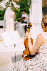 Girl musician sits near the music stand and holds a violin during the wedding ceremony, back view