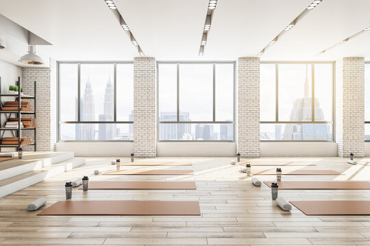 Contemporary concrete yoga gym interior with equipment, daylight and wooden flooring. Healthy lifestyle concept. 3D Rendering.