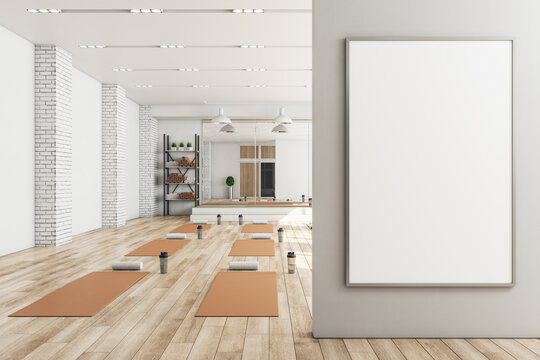 Modern concrete yoga gym interior with equipment, blank banner on wall, daylight and wooden flooring. Healthy lifestyle concept. Mock up, 3D Rendering.