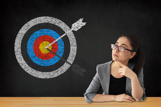 Business woman and target with arrow sign on blackboard