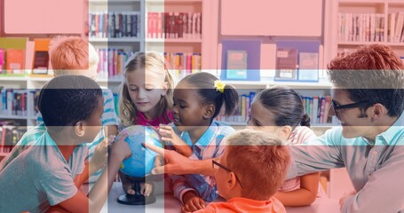 Composition of norwegian flag over smiling male teacher looking at globe with children in library