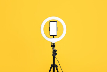 Modern tripod with ring light and smartphone on yellow background
