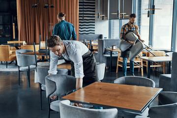 Fototapeta Handsome young men in aprons arranging furniture while preparing restaurant to opening obraz