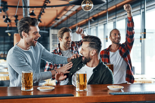 Cheering young men in casual clothing drinking beer and watching sport game while sitting in the pub