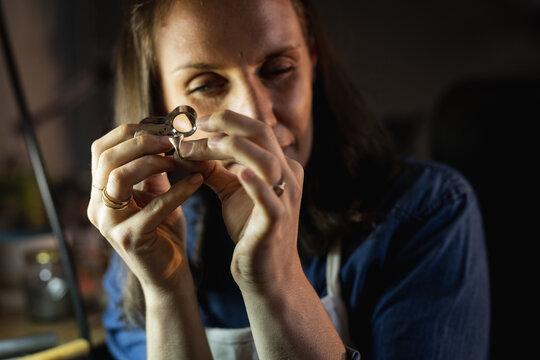 Portrait of caucasian female jeweller wearing apron, making jewelry in workshop