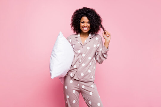 Photo of adorable pretty wavy dark skin lady dotted sleepwear arm curl holding white pillow isolated pink color background