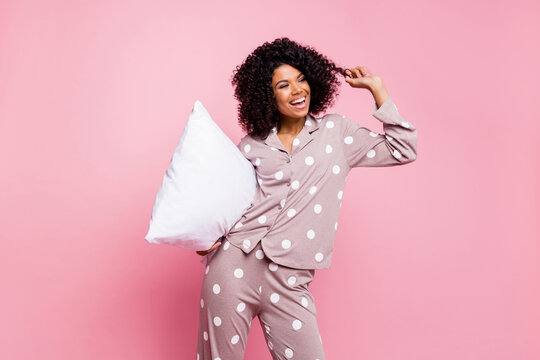 Photo of charming cute curly dark skin woman dotted nightwear holding white pillow dancing arm curl isolated pink color background
