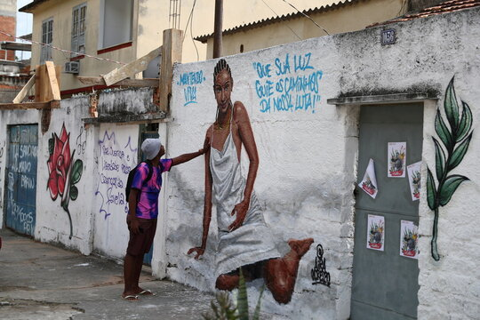 A man touches a graffiti made by artists in honor of Kathlen de Oliveira Romeu, who was pregnant and was shot dead during a police operation, according to local media, at the Lins slums complex in Rio de Janeiro