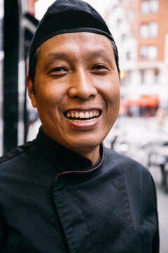 Portrait of an asian chef laughing in a street in Bilbao, Spain
