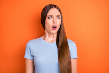 Photo of scared long hairdo young lady open mouth wear blue t-shirt isolated on vivid orange color...