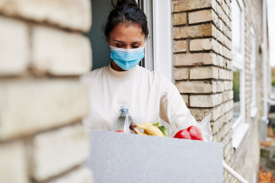 Woman carrying a grocery delivery box